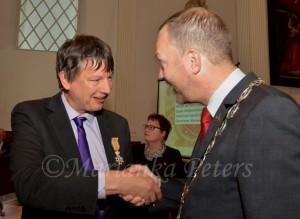Burgemeester Schoenmaker van Gouda feliciteert Paul Abels met zijn koninklijke onderscheiding.