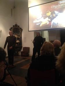 Maarten van Rossum tijdens zijn lezing over de lezende zusjes. Rechts museumdirecteur Gerard de Kleijn