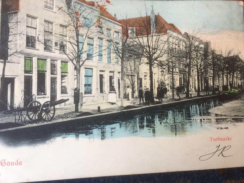 De Turfmarkt in 1903. Goed zichtbaar zijn de twee kleine huisjes en daarna de smalle poort naar de (niet zichtbare) gereformeerde kerk. Daarnaast de twee huizen die in 1965 moesten wijken voor het Brandpunt, met rechts de woning van dokter Büchner.